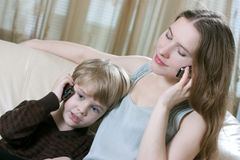 Family phone talking. Cute little boy and his mother are sitting on the sofa and talking by cell phone Stock Photo