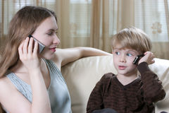 Family phone talking. Cute little boy and his mother are sitting on the sofa and talking by cell phone Royalty Free Stock Photo