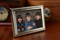 Family photo. Framed photo on wooden desk of three smiling children Stock Photos