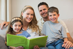 Family with photo album sitting on sofa Stock Images