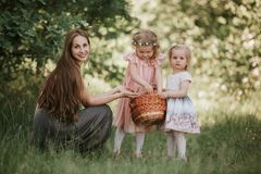 Family photo mom with daughters in the park. Photo of young mother with two cute kids outdoors in spring time royalty free stock images