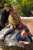 Family photo. Picture of two brothers and their sister in a turtle shell Stock Image