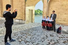 Family photo session on the ancient  Khaju bridge, Isfahan, Iran. Isfahan, Iran - April 24, 2017: An unknown man photographs an Iranian family, a father with Stock Photo