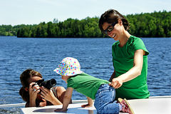 Family Photo Shoot. A photographer takes pictures of a one-year-old girl on the deck of a houseboat on a lake Royalty Free Stock Photos