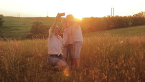Family is photographed in a field at sunset. Mother and two sons on vacation make selfie. Traveling on vacation stock footage