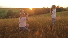 Family is photographed in a field at sunset. Mother and two sons on vacation make selfie. Traveling on vacation stock video footage