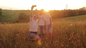 Family is photographed in a field at sunset. Mother and two sons on vacation make selfie. Traveling on vacation stock video