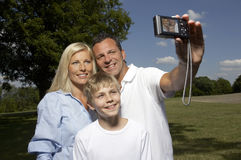 Family photographing themselves in park Royalty Free Stock Image