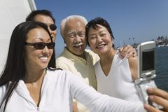 Family photographing themselves on sailboat Stock Photography