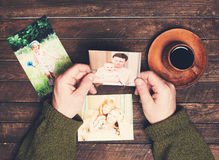 Family photos in man hands and on weathered wooden table. Father stock photo