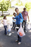 Family Picking Up Litter In Suburban Street Royalty Free Stock Photos