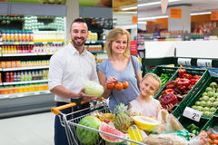 Family picking veggies in food store Stock Photos
