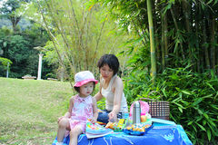 Family picnic. Mother teach her daughter reading a book at garden Royalty Free Stock Photography