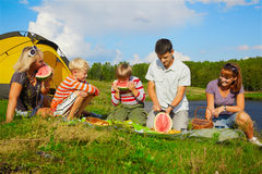 Family picnic. Outdoor portrait of happy families at the picnic eating watermelon Royalty Free Stock Photos