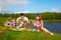 Family picnic. Outdoor portrait of happy families eating watermelon at the picnic near camp tent Stock Photography