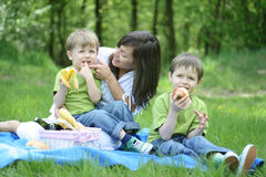 Family picnic. Mother and sons relaxing - family picnic in the forest stock photo