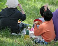 Family picnic. A Japanese family eating outdoor during early spring season-hanami party Royalty Free Stock Photography