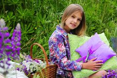 Family picnic. Basket with flowers and next to a beautiful little girl with cushions Royalty Free Stock Photos