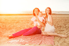 Family at a picnic on the beach. Mother, father and baby near th Royalty Free Stock Photos