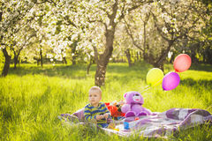 Family picnic.child sitting among toys. On blanket in spring garden in warm sunny day. family portrait. sunset people. happy family concept. people on weekend royalty free stock images