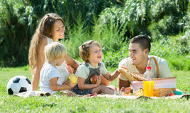 Family on picnic at countryside. Vacation day of young cheerful family with picnic at countryside in summer day stock image
