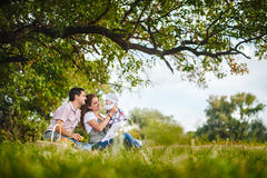 Family picnic in countryside. Young parents with their baby girl having a picnic under a tree in the countryside Royalty Free Stock Photos