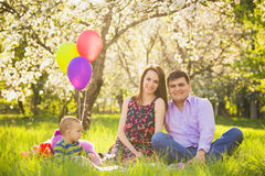 Family picnic. father, mother, child sitting together. On blanket in spring garden in warm sunny day. family portrait. sunset people. happy family concept Stock Photo