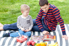 Family picnic. Handsome young father and his son having fun time together at picnic outside Stock Image