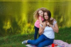 Family picnic. Mother and daughter. Sit on blanket on banks of river. Little girl hugs mother. Apples are lying on blanket. Time together stock photography