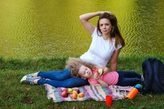 Family picnic. Mother and daughter. Sit on blanket on banks of river. Little girl lying on her mother`s lap and eating fruit. Apples are lying on blanket. Time royalty free stock photography