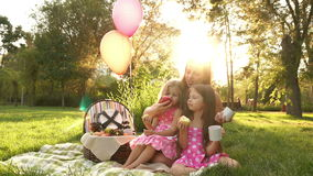 Family picnic. Mother and two daughters are sitting on the grass in a summer park at sunset. They eat fruit. Family time. The concept of a happy family stock footage