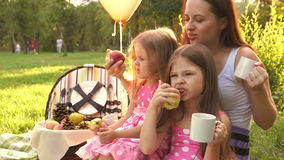 Family picnic. Mother and two daughters sitting on the grass in the summer park at sunset. They eat fruit. Family time. The concept of a happy family stock footage