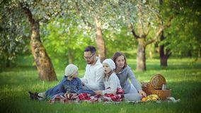 Family picnic in the Park on the grass. Cheerful family sitting on the grass during a picnic in a park, all have breakfast. there is a basket with meal. Fresh stock video footage