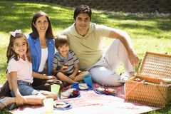 Family picnicing. Hispanic family picnicking in the park and smiling at viewer royalty free stock photo