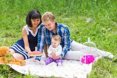 Family picnicking outdoors with their cute daughter royalty free stock photo