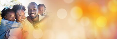 Family piggy back outside with orange bokeh transition stock photography