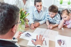 Family planning their kitchen with experienced expert in the shop. Looking at the plan stock photography