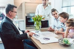 Family planning their kitchen with experienced expert in the shop royalty free stock photo