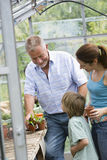 Family Planting In Greenhouse Stock Images