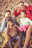Family play with fall leaves. Happy young family on fallen leaves Royalty Free Stock Images