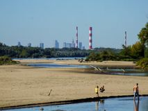 Family playing over Wisła. City of Warsaw in the background. Family playing in Wisła water. City of Warsaw in background. Riverbank of Vistula in Jozefow near Royalty Free Stock Images
