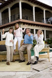 Family playing air guitar on patio Royalty Free Stock Photography
