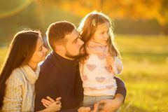 Family playing in autumn park having fun. Girl playing at sunset in park with parents Royalty Free Stock Photography