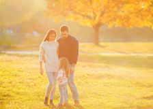 Family playing in autumn park having fun. Girl playing at sunset in park with parents Stock Photo