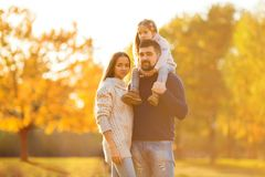 Family playing in autumn park having fun. Girl playing at sunset in park with parents Royalty Free Stock Image