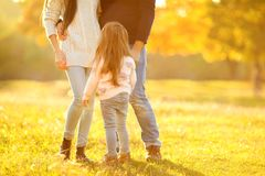 Family playing in autumn park having fun. Girl playing at sunset in park with parents Stock Photography