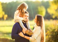 Family playing in autumn park having fun. Park at sunset of the day Stock Photo