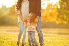 Family playing in autumn park having fun. At sunset.Girl playing at sunset in park with parents Stock Images