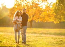 Family playing in autumn park having fun. Girl playing at sunset in park with parents Royalty Free Stock Photos