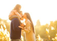 Family playing in autumn park having fun kisses. Park at sunset of the day Royalty Free Stock Image